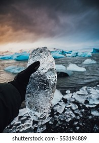 A man holding a chunk of ice in the hand,  Jokulsarlon glacial lagoon Iceland