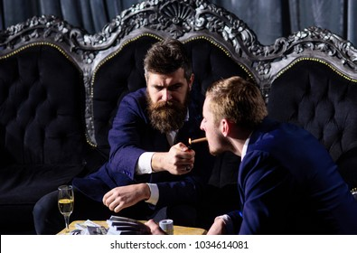 Man holding a cigar and smoking it with friend. Man holding cigar in his hand enjoying his life.