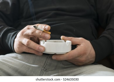 Man holding a cigarette and ashtray. Close up