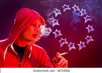 Man, holding a cigarette, blowing rings in the shape of the 12 stars of the European Union