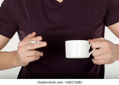 Man holding a cigarette in hand with cup of coffee