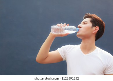 man holding clean fresh mineral water bottle with court background, drinking water outdoor under summer heat. Health care, Well being, Thirst Refreshment, Water Balance in body is medicine concept