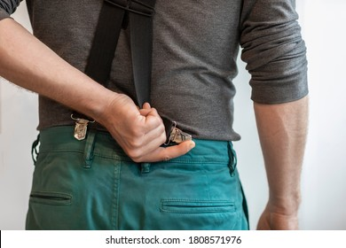 A man holding a clip of his suspenders and attaching it to his green trousers. Modern hipster formal fashion style. Close-up of a hand and clothing