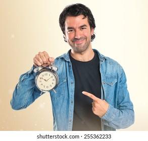 Man holding a clock over ocher background