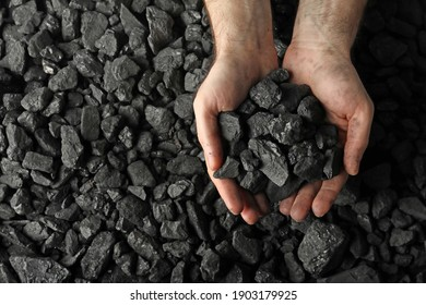 Man holding coal in hands over pile, top view. Space for text