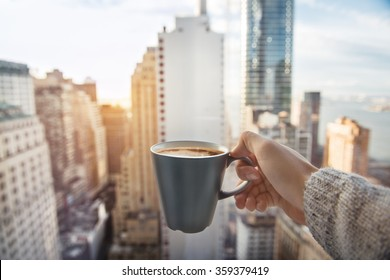 Man holding coffee cup in luxury penthouse apartments with view to New York City Manhattan downtown at the morning
