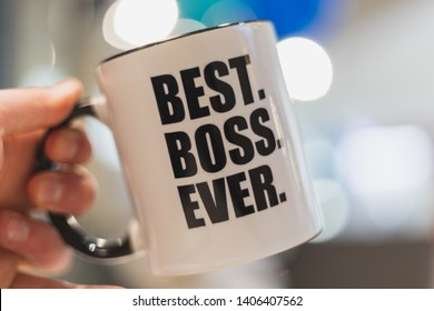 A man holding a coffee mug with best boss ever printed on it.