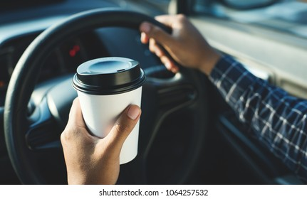 Man holding coffee paper cup in car