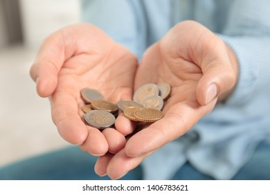 Man holding coins in hands indoors, closeup