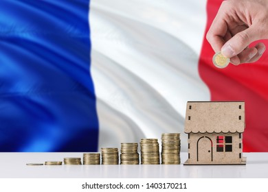 Man holding coins putting in wooden house moneybox, France flag waving in the background. Saving money for mortgage.
