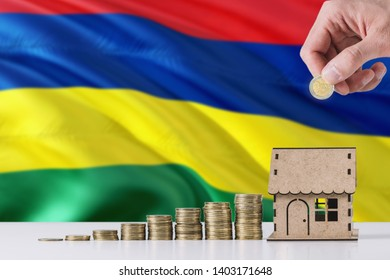 Man holding coins putting in wooden house moneybox, Mauritius flag waving in the background. Saving money for mortgage.