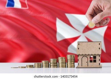 Man holding coins putting in wooden house moneybox, Wallis And Futuna flag waving in the background. Saving money for mortgage.