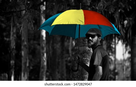 Man holding a colourful umbrella standing in a place