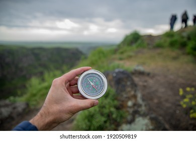 man holding compass in nature background