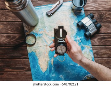Man holding a compass over a map and planning to travel, point of view. Focus on the compass. The map is blurred