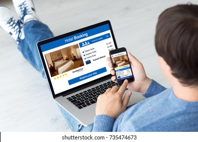man holding computer and phone with app hotel booking