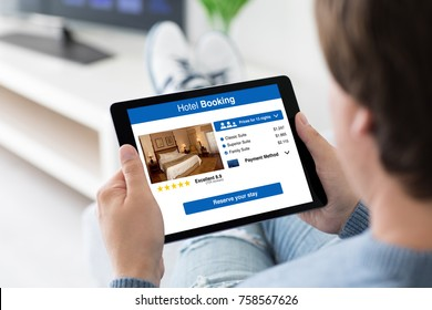 man holding computer tablet with app hotel booking on screen in room