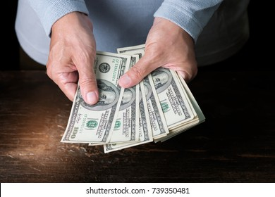 Man holding and counting cash at old wooden table   ,business concept. US bank note.
