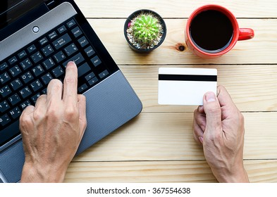 Man holding credit card in hand and entering security code using laptop keyboard.Online shopping concept.Beautiful hand holding credit card.Man using laptop computer on desk table.