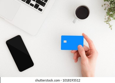 Man holding credit card over white office desk with smartphone and laptop. Top view.