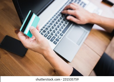 Man holding a credit card and typing. On-line shopping on the internet using a laptop