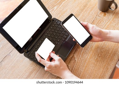man holding credit card and using mobile phone and laptop computer with blank white screen for online shopping