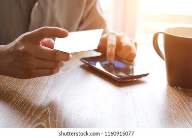 man holding credit card and using mobile smart phone for online shopping
