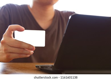 man holding credit card and using laptop computer for online shopping