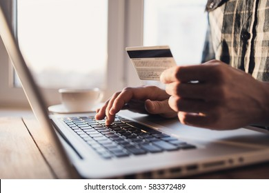 Man holding credit card and using laptop. Online shopping concept