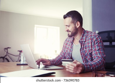Man holding credit card and using laptop. Online shopping