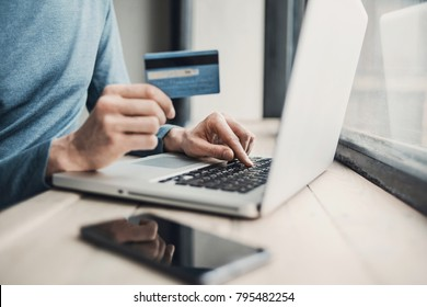 Man holding credit card and using laptop. Online shopping, business and technology concept.