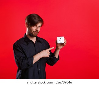 Man holding a cube with the number four. Numerals. The man points his index finger on the cube. Call to action