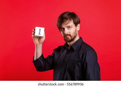 Man holding a cube with the number one. Always first. Numerals. Man teaches the basics of mathematics.
