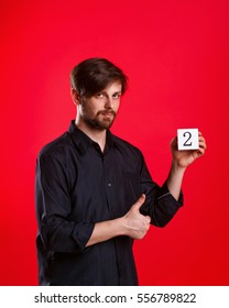 Man holding a cube with the number two. Numerals. Man showing thumb up.