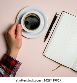 Man holding cup of coffee by left hand. Left hander day concept. Working place of lefty
