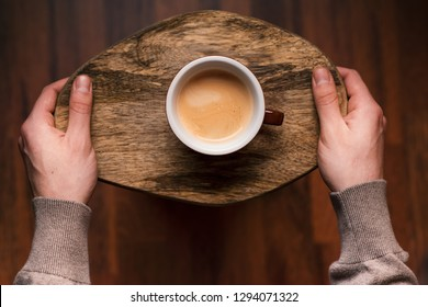 Man holding a cup of coffee on a wooden, vintage background. Hand of young businessman holding a mug of coffee. Vintage tones.