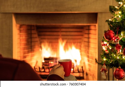 Man holding a cup of coffee on Christmas tree and blur burning fireplace background