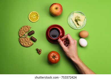 Man holding a Cup of coffee surrounded by different food on a colored background