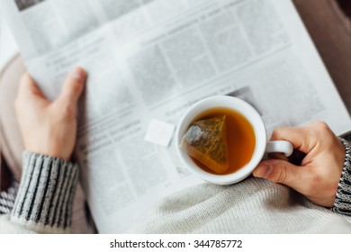 Man holding a cup of tea and reading newspapers near the window