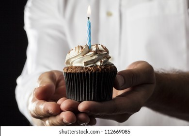 A Man holding a cupcake with a candle in a gesture of giving.