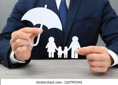 Man holding cutout paper family and umbrella at table, closeup. Life insurance concept