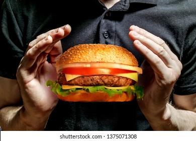 A man holding a delicious juicy hamburger