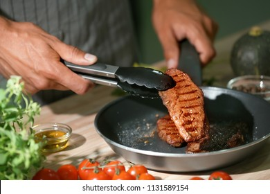 Man holding delicious roasted meat with tongs in kitchen, closeup