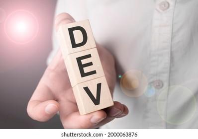 Man holding dev word on wooden cube. - Shutterstock ID 2000063876