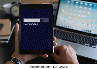 Man holding digital tablet with mobile apps downloading on futuristic technology screen with laptop computer as background, close up