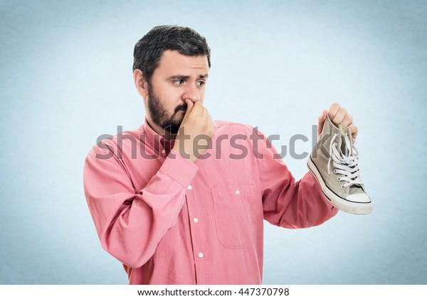汚い悪臭のする靴を持つ男性。悪臭がする