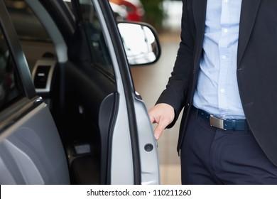 Man holding a door open in a car dealership