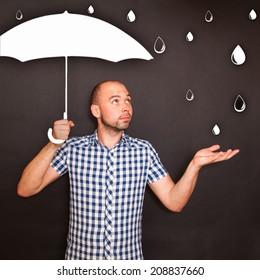 Man holding drawn umbrella in the rain
