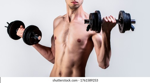 Man holding dumbbell in hand. Skinny guy hold dumbbells up in hands. A thin man in sports with dumbbells. Weak man lift a weight, dumbbells, biceps, muscle, fitness. Nerd maleraising a dumbbell.