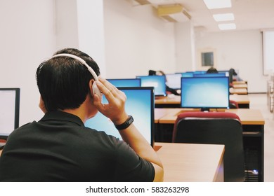 Man holding earphones in class room